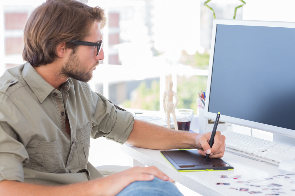 Artist using graphics tablets sitting at desk